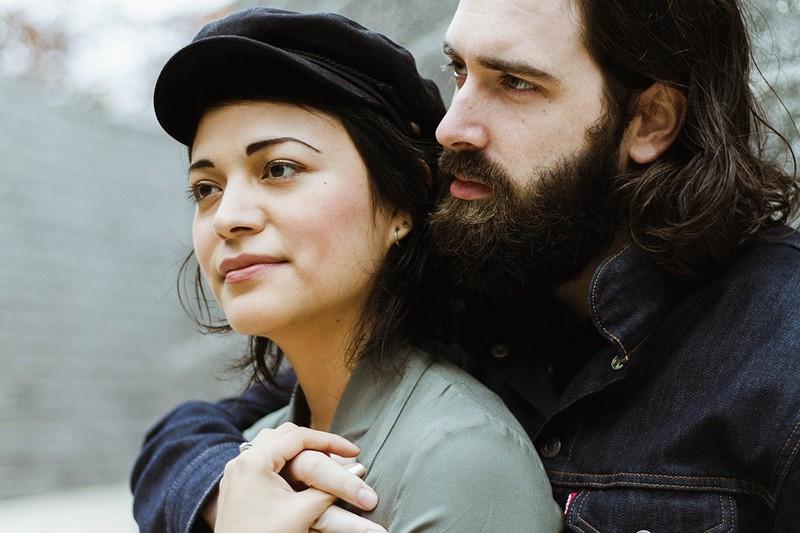 Ein Mann umarmt eine nachdenkliche Frau von hinten, während er draußen steht