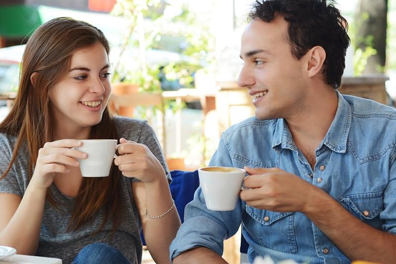 Ein Mann und eine Frau genießen einen Kaffee im Café und schauen sich an