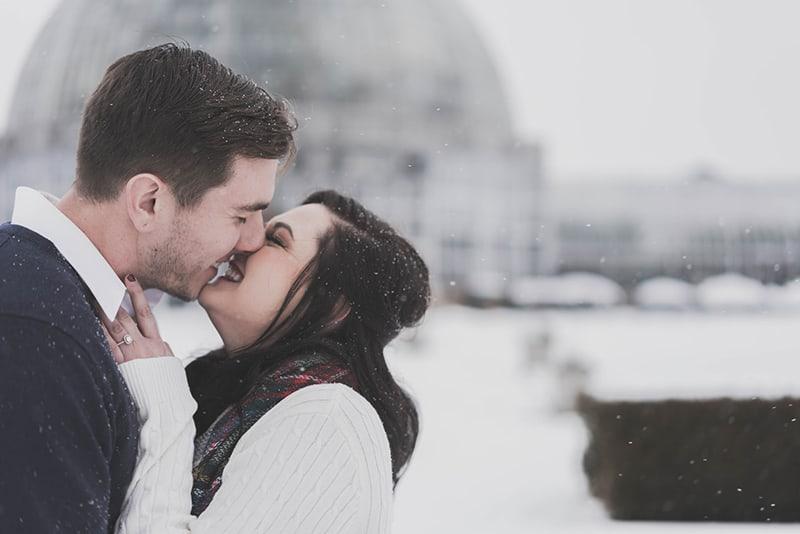 Ein Mann und eine Frau küssen sich, während sie im Schnee stehen