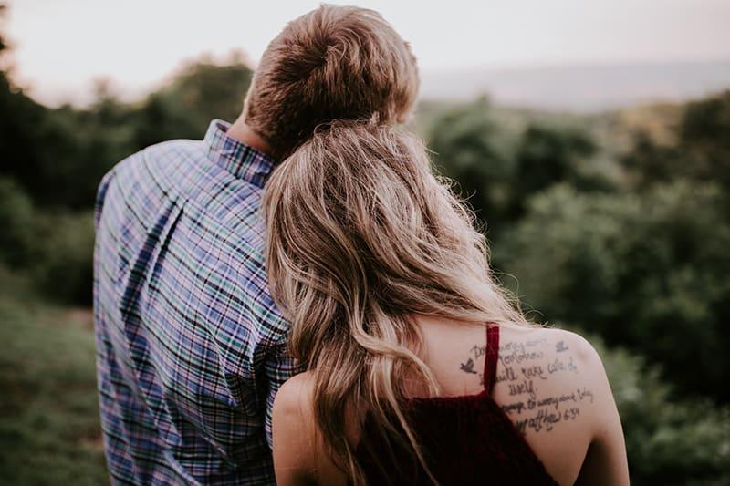 Ein Mann und eine Frau lehnen sich aneinander, während sie stehen und dem Wald zugewandt sind
