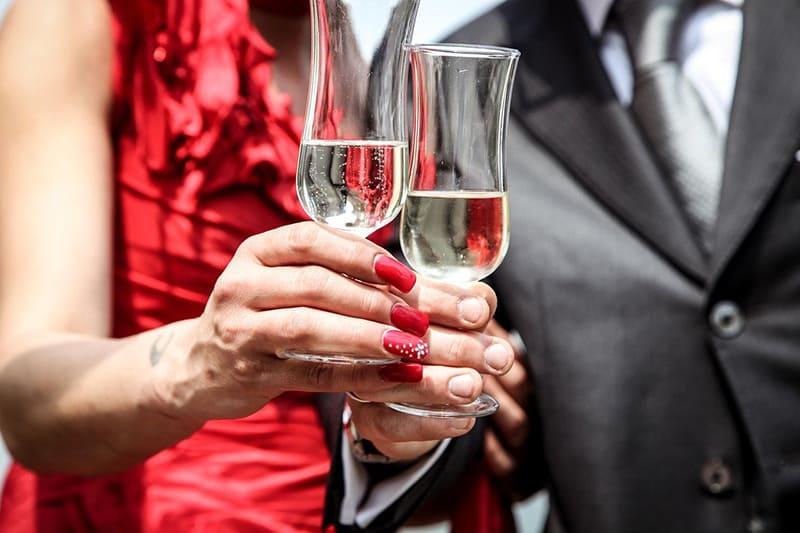 Ein Mann und eine Frau machen einen Toast mit einem Glas Champagner, während sie nahe beieinander stehen