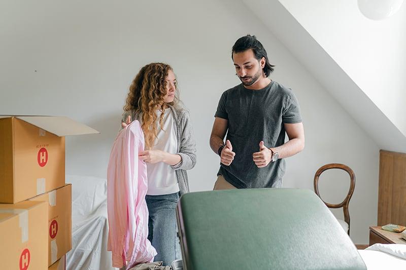 Ein Mann und eine Frau packen einen Koffer aus und betrachten das rosa Hemd