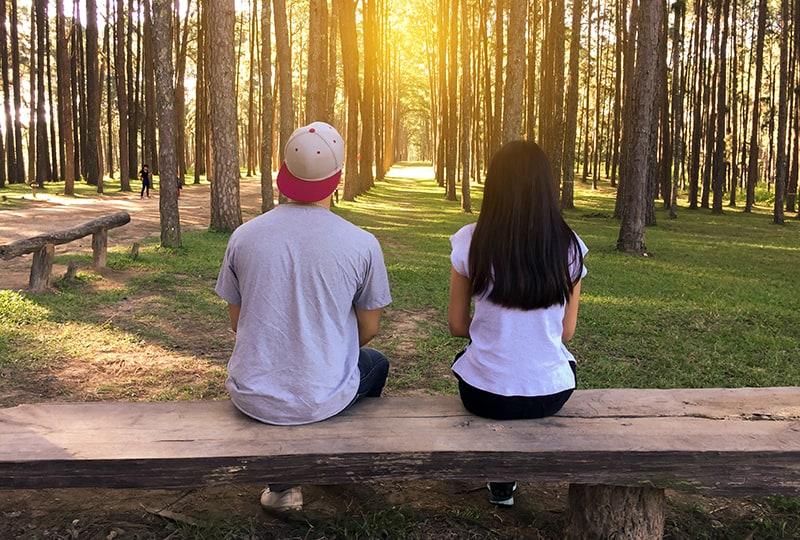 Ein Mann und eine Frau sitzen auf der Bank mit Platz zwischen ihnen im Park