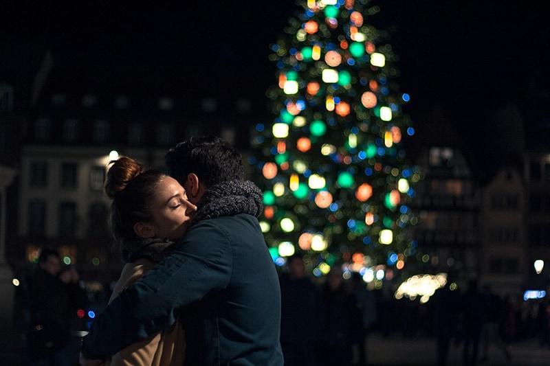 Ein Mann und eine Frau umarmen sich in der Nacht in der Nähe des Weihnachtsbaumes