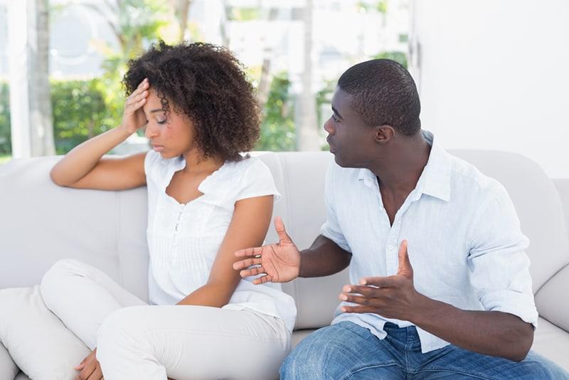 Ein Paar hat einen Streit, während es zu Hause auf der Couch sitzt