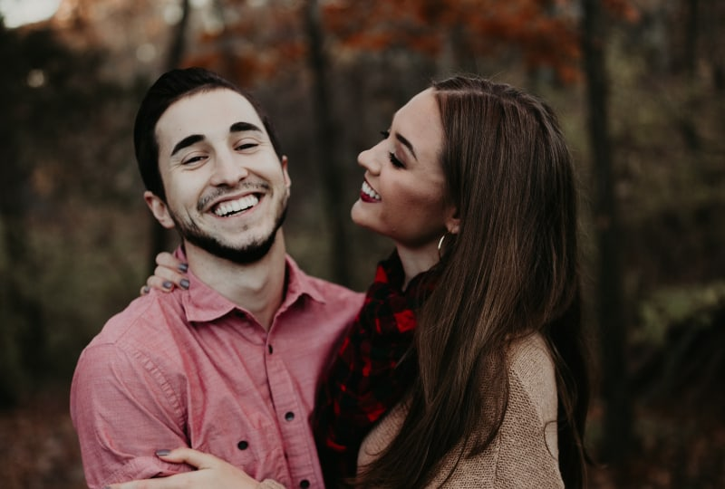 Ein Paar lacht und geht im Wald spazieren