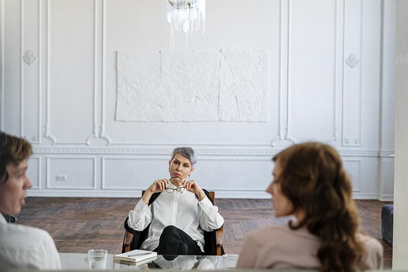 Ein Therapeut sitzt im Sessel und schaut zu einem Paar, das vor ihr spricht