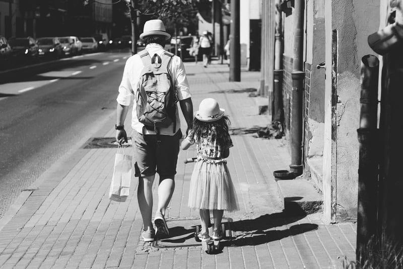Ein Vater und eine Tochter gehen die Straße entlang
