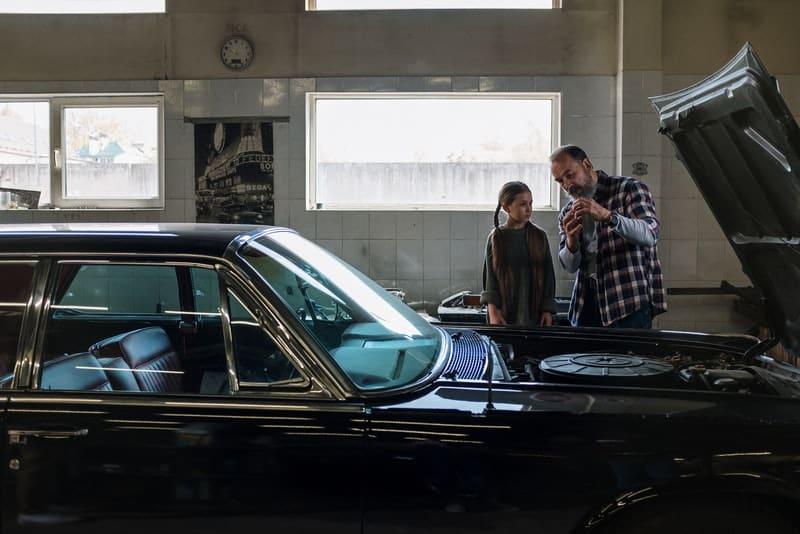 Ein Vater und eine Tochter in einer Garage reparieren ein Auto