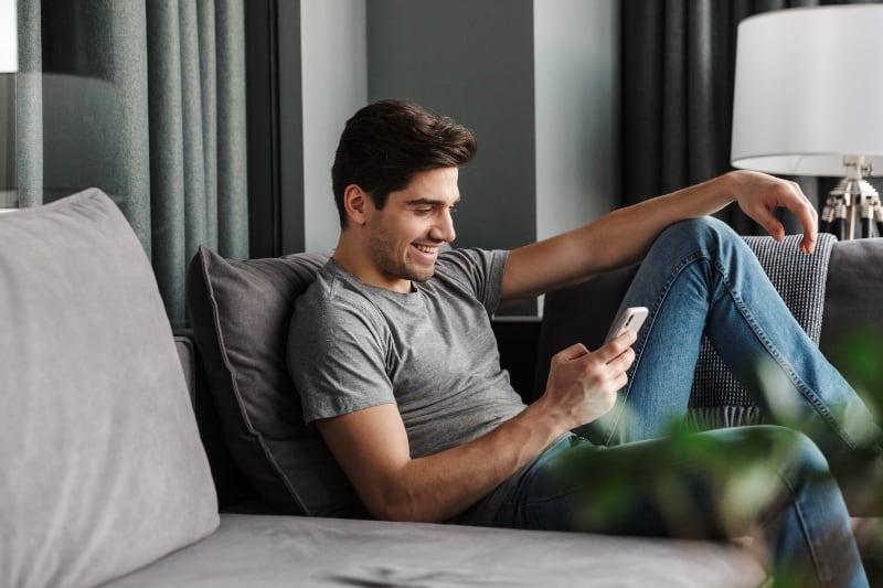 Ein attraktiver Mann mit Bart benutzt ein Handy
