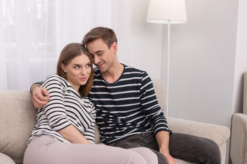 Ein aufgeregtes Paar kuschelt sich auf die Couch