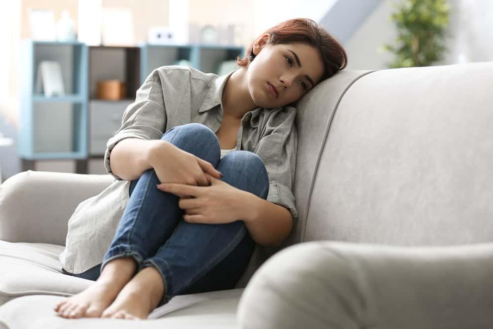 Ein depressives schwarzhaariges Mädchen sitzt auf der Couch