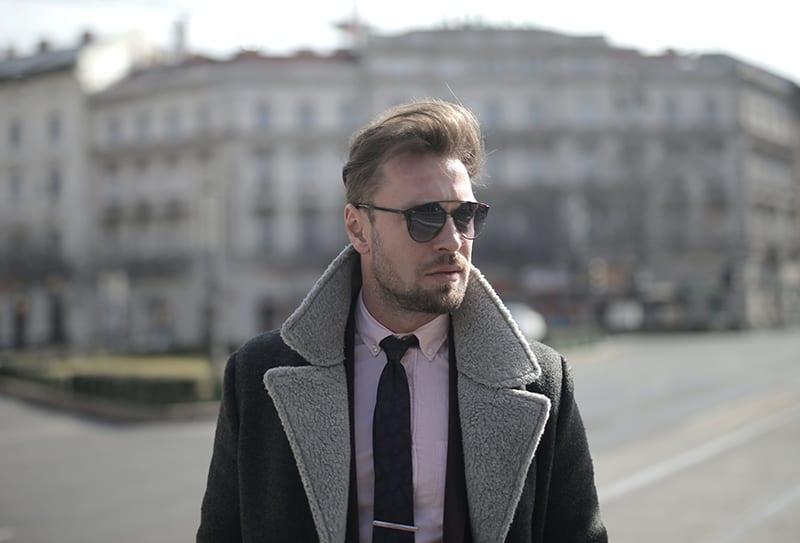 Ein ernster Mann mit Sonnenbrille stand auf der Straße