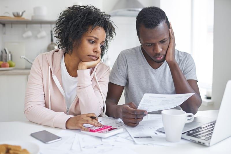 Ein gestresster Mann und eine gestresste Frau verwalten gemeinsam Rechnungen, während sie am Tisch sitzen