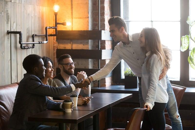 Ein glückliches Paar trifft sich mit Freunden im Café