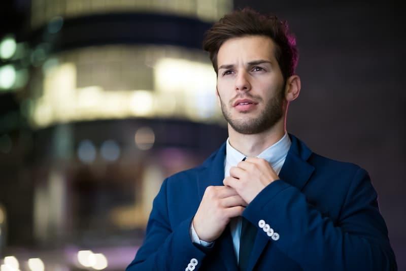 Ein hübscher Geschäftsmann stimmt seine Krawatte