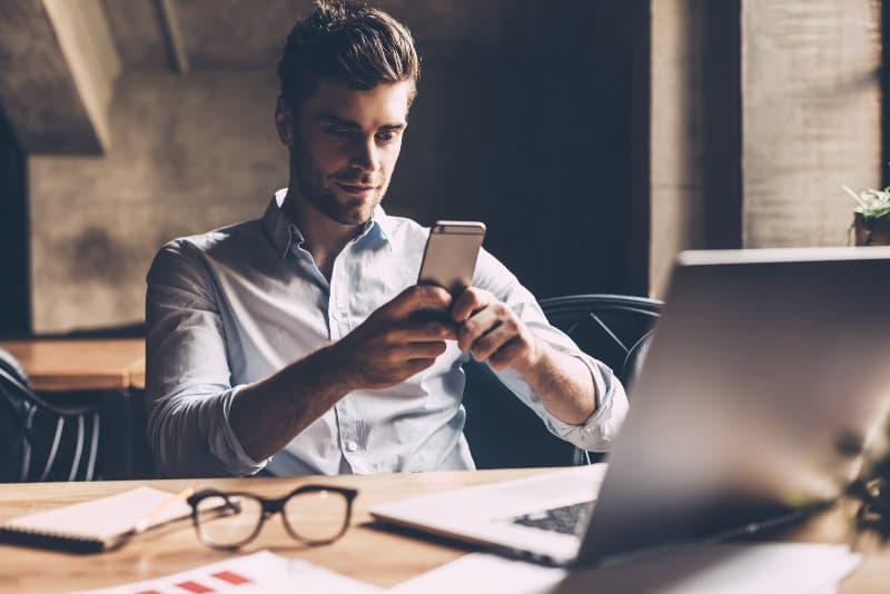 Ein junger Mann sitzt bei der Arbeit und tippt eine Nachricht auf sein Handy