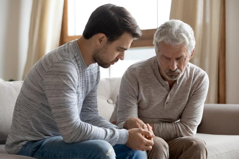 Ein junger trauriger Mann hält die Hand seines Vaters