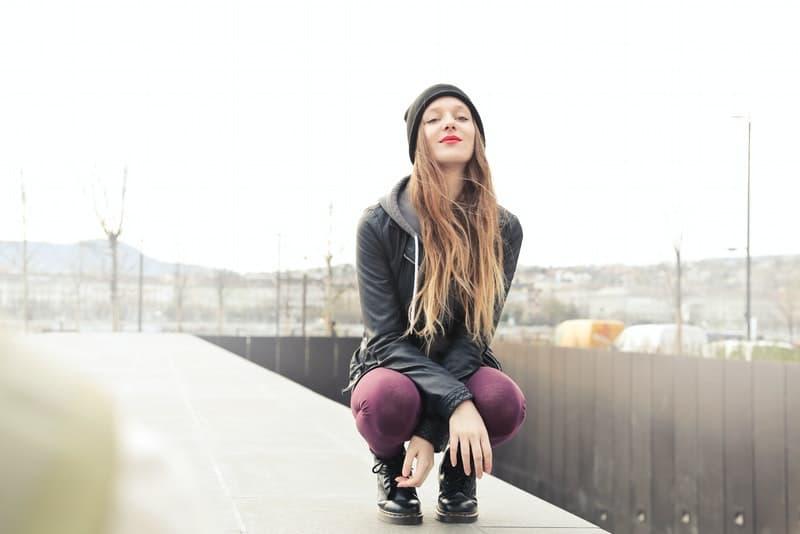 Ein junges Mädchen hockt auf der Terrasse