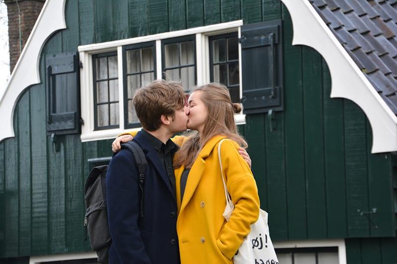 Ein junges Paar küsst sich, während es tagsüber vor dem Haus steht