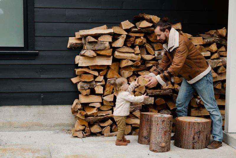 Ein kleines Mädchen hilft ihrem Vater beim Stapeln von Holz
