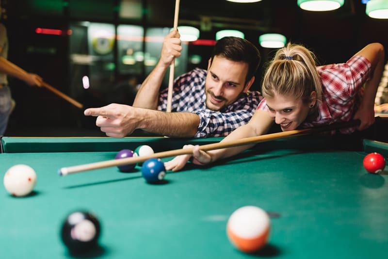 Ein lächelnder Mann, der eine Frau berührt, wie man Snooker spielt, während er zusammen in der Bar rumhängt