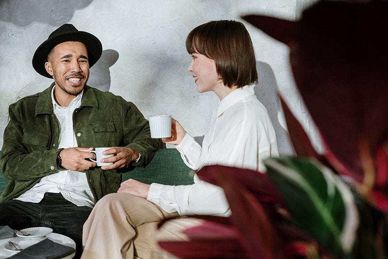 Ein lächelnder Mann, der mit einer Frau über ein Date spricht, während er zusammen Kaffee trinkt