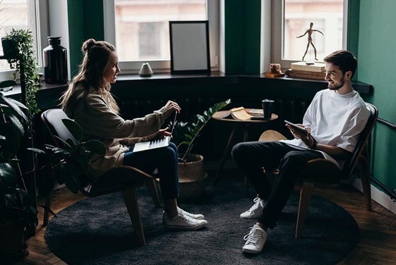 Ein lächelnder Mann spricht mit einer Frau, während beide ihre Geräte benutzen