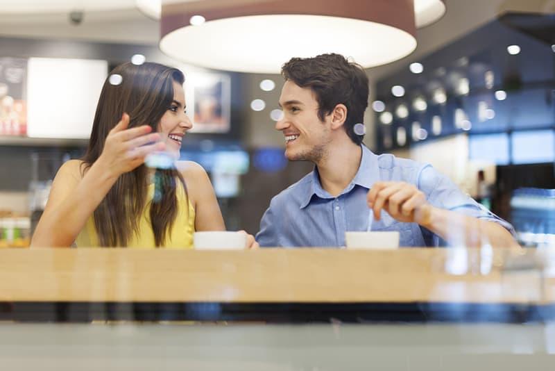 Ein lächelnder Mann hört einer Frau zu, die mit ihm spricht, während sie im Café Kaffee trinkt