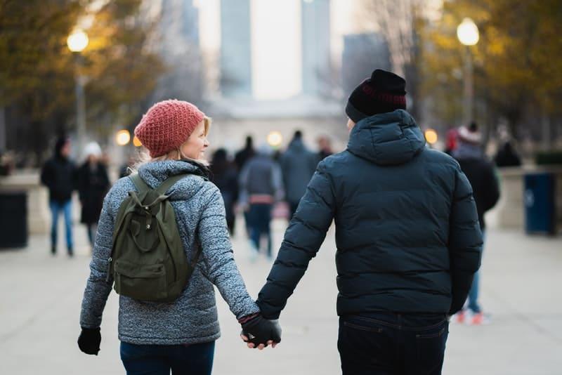 Ein liebendes Paar geht Händchen haltend die Straße entlang