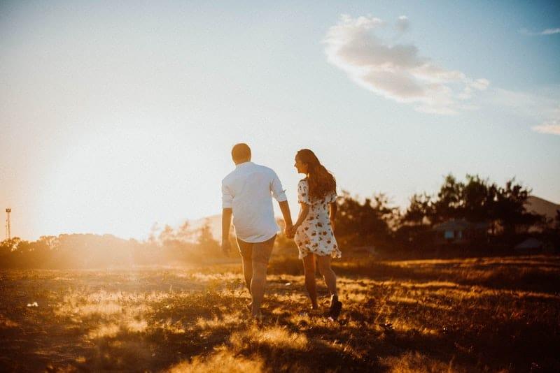 Ein liebendes Paar geht über ein Feld in der Sonne