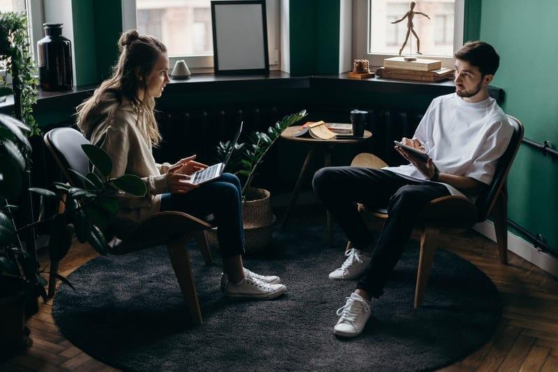 Ein liebevolles Paar sitzt in einem Raum und arbeitet über Laptops und Tablets