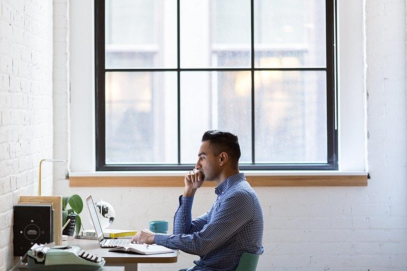 Ein nachdenklicher Mann, der im Büro am Laptop arbeitet