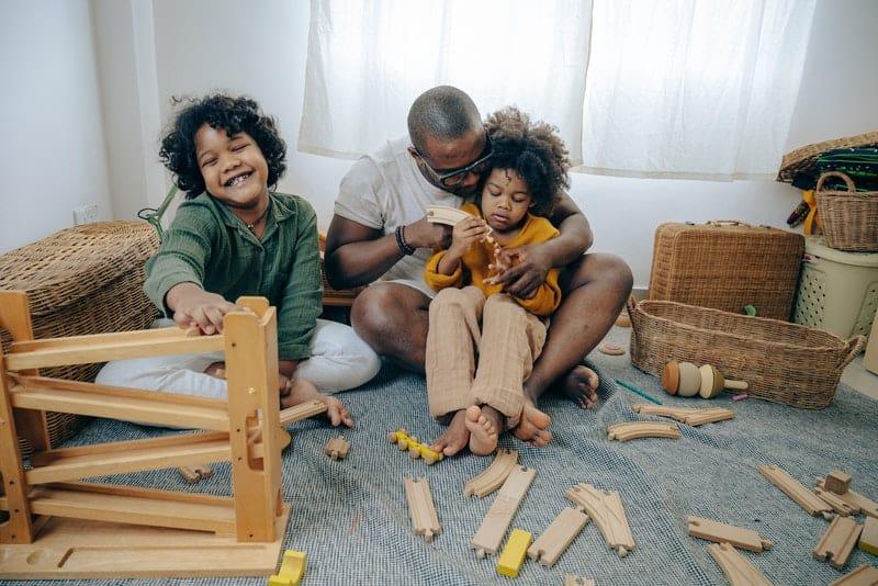 Ein schwarzer Mann mit seinen Töchtern sitzt auf dem Boden