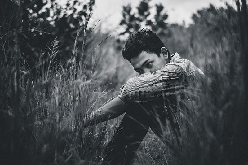 Ein trauriger Mann, der sich auf die Knie stützte, während er auf der Wiese saß
