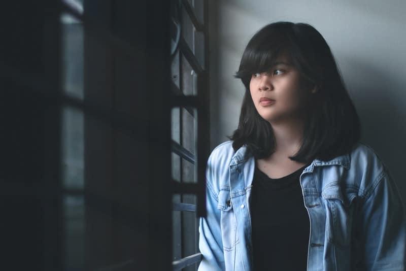Ein trauriger Teenager schaut aus dem Fenster