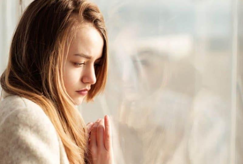 Ein-trauriges-Mädchen-schaut-aus-dem-Fenster(1)