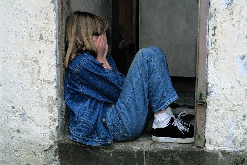 Ein trauriges kleines Mädchen sitzt am Fenster und weint