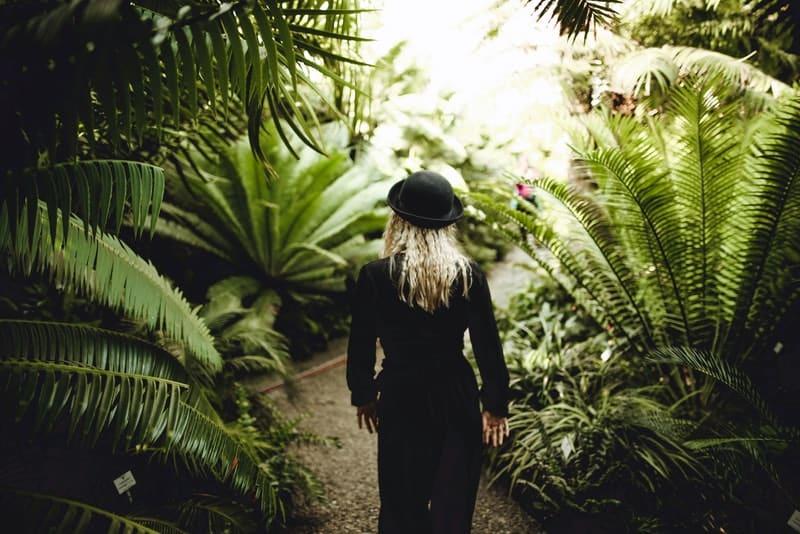 Eine Blondine mit einem schwarzen Hut geht durch den Wald