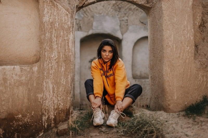 Eine Brünette in einem gelben Sweatshirt sitzt zwischen den Wänden