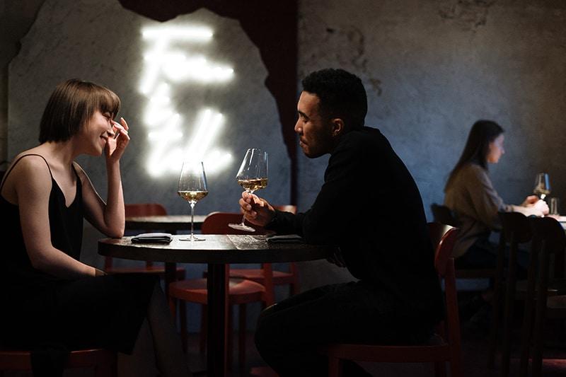 Eine Frau berührt ihr Gesicht, während sie mit einem Mann im Restaurant sitzt und zusammen Wein trinkt