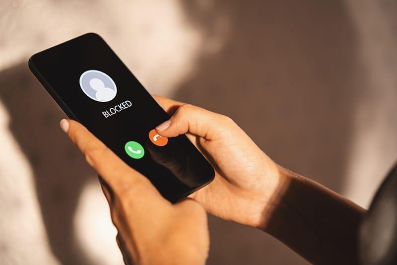 Eine Frau blockiert eingehende Anrufe auf dem Smartphone