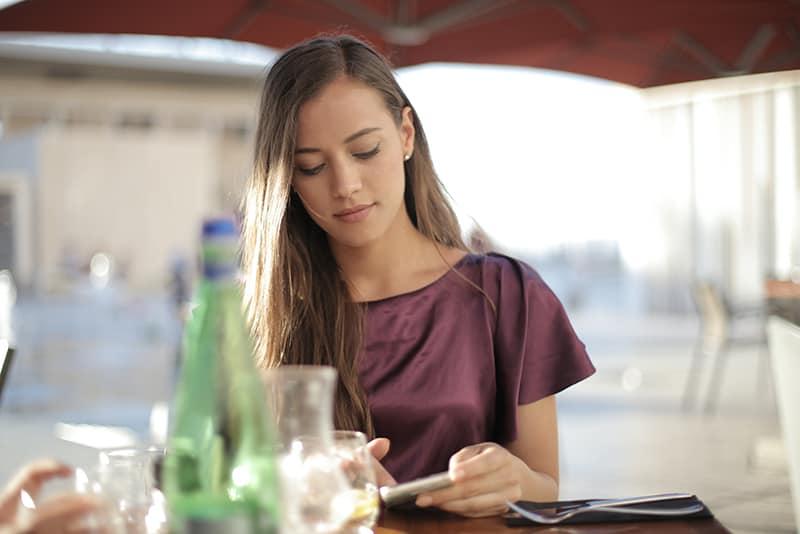 Eine Frau, die einen Anruf ablehnt, während sie alleine im Café sitzt