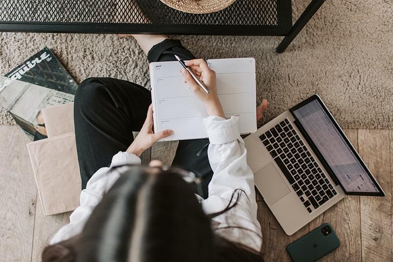 Eine Frau, die einen Stift und ein Notizbuch hält, während sie auf dem Boden sitzt