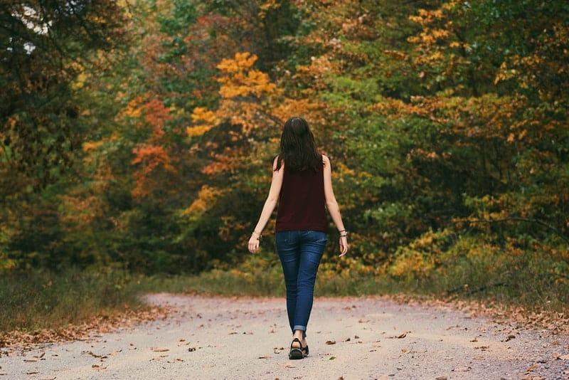 Eine Frau in einem braunen T-Shirt und Jeans geht durch den Wald