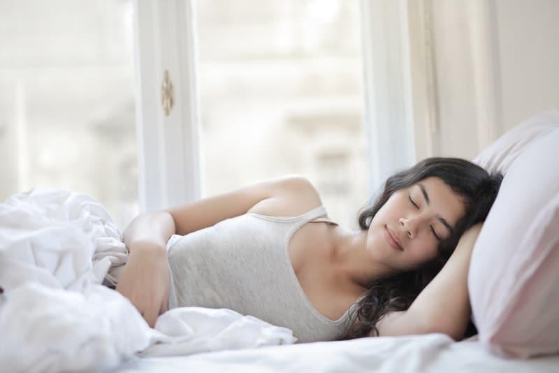 Eine Frau in einem grauen Unterhemd schläft auf dem Bett