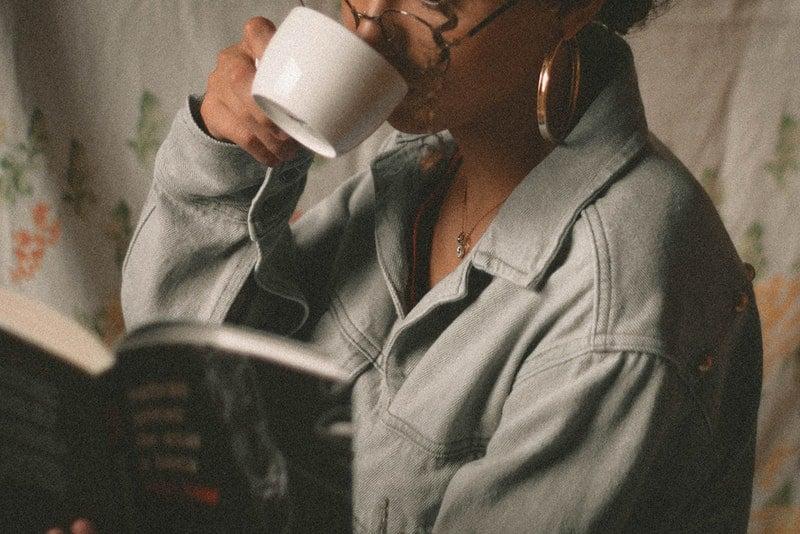 Eine Frau liest ein Buch und trinkt Tee