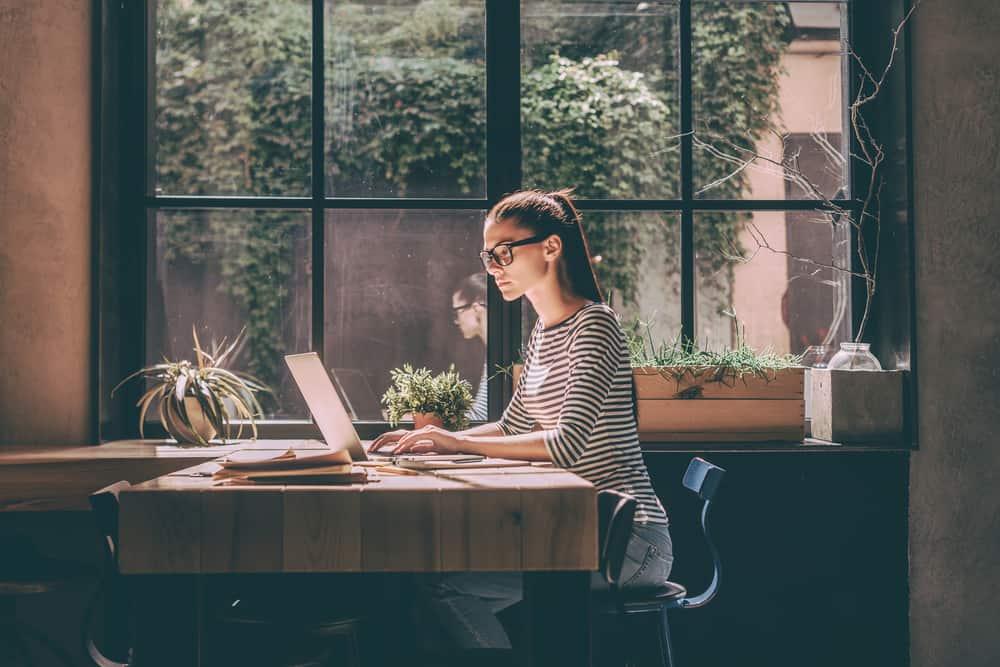 Eine Frau mit Brille sitzt an einem Tisch und benutzt einen Laptop