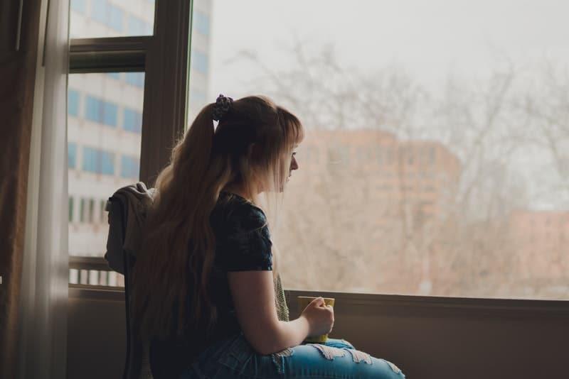 Eine Frau mit Tee in der Hand sitzt am Fenster