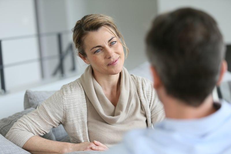 Eine Frau mittleren Alters spricht mit ihrem Mann auf der Couch